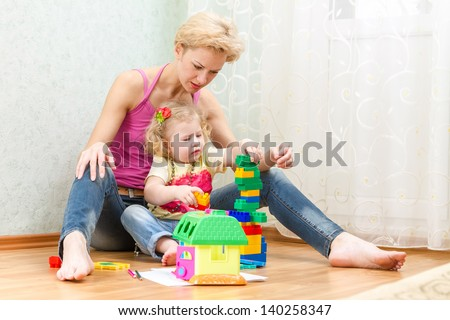 Mother with a little daughter playing with blocks
