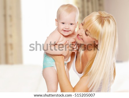 Mother with baby at home. Happy family with newborn indoors