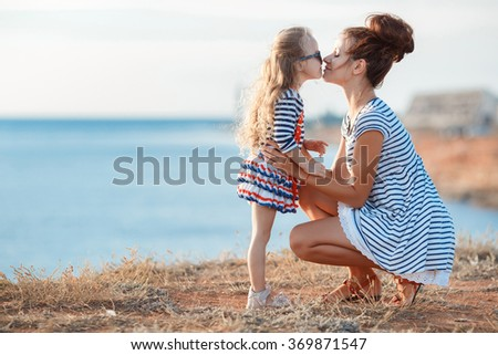 mother with child girl by the sea. Sunset portrait. Outdoor. Summer. Woman with girl. Happy family relaxing by sea. Relaxed young mother standing on the shore with her playful little daughter.