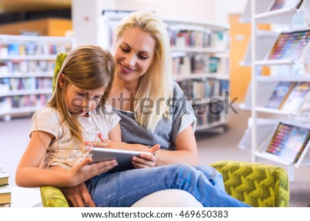 Mother with daughter look at their touch pad tablet device together in library. Happy family, preschool concept. Parent educating children.