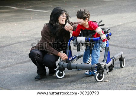 Mother with disabled son walking outdoors with walker, medical mobility equipment