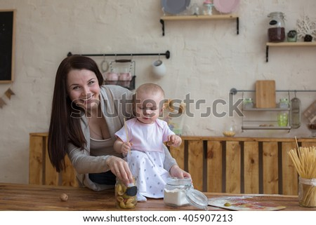 mother with her baby daughter in the kitchen together cooking, lifestyle real home interior casual