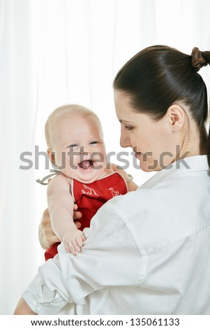 Mother with her happy child on arms on white background