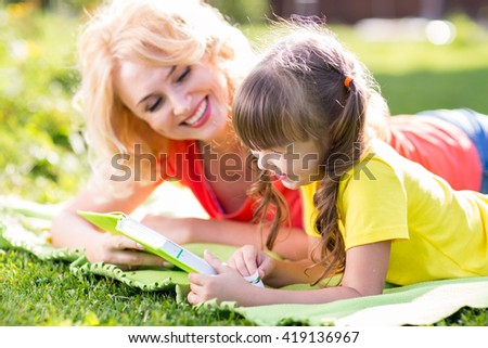 Mother with kid daughter lying in summer park