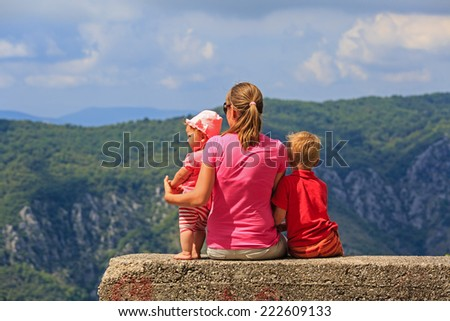 mother with kids having rest on vacation in mountains