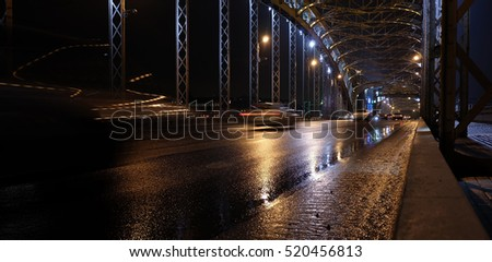 Motion blur. Night traffic on old riveted metal bridge. Bolsheokhtinsky Bridge (or Peter the Great Bridge), November, Saint-Petersburg, Russia