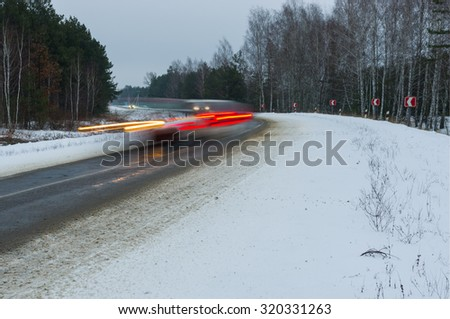 Motion blur of a speedy cars on winter road turn