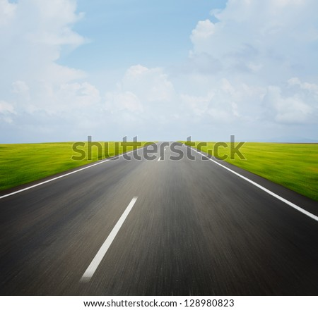 Motion blurred asphalt road through green meadow with blue cloudy sky on the background