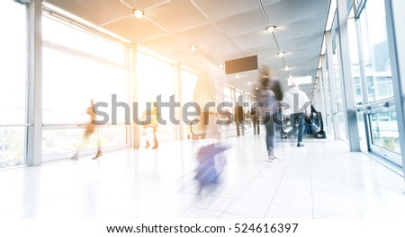 motion blurred commuters in a airport corridor