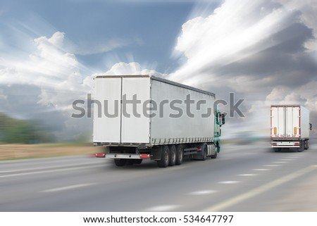 Motion blurred image of truck traffic on the highway in the sun