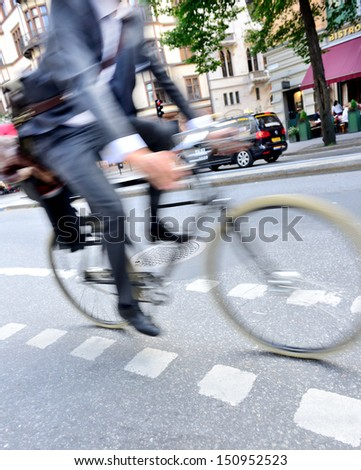 Motion blurred man in suit on bike