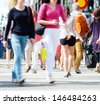Motion blurred pedestrians crossing sunlit street - stock photo