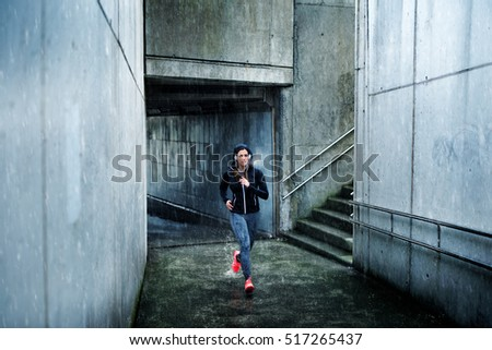 Motivated sporty woman running on winter under heavy raining and cold weather. Female urban athlete exercising.