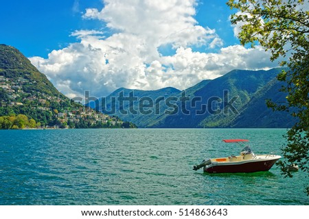 Motor Boat at the embankment of the luxurious resort in Lugano on Lake Lugano and Alps mountains in Ticino canton of Switzerland.