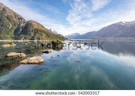 Mountain and lake background: clear blue water in pacific ocean in south America with mountain and blue sky with ice floating in the sea for nature background