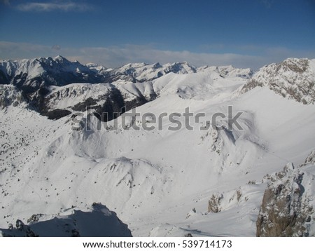 mountain hiking trail in the italian Alps with snow and ice