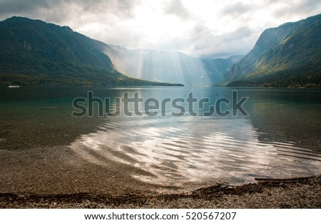 mountain lake with sunrays on the misty morning, bohinj, slovenia