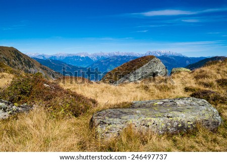 mountain landscape with green grass, rocks and blue sky