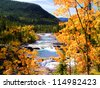 Mountain river view framed by yellow autumn leaves - stock photo
