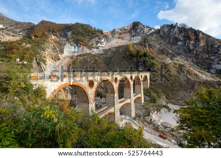 Mountain with marble mines and an old train bridge near Carara in italy