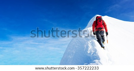 Mountaineer arrive to the summit of a snowy peak. Concepts: determination, courage, effort, self-realization. Clear sky, sunny day, winter season. Large copy-space on the left. European Alps, Europe.