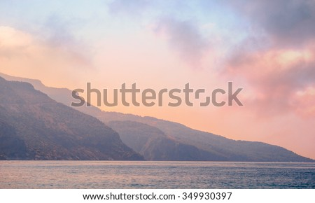 Mountains landscape at sunrise - cloudy sky in pastel colors for your design, serenity and rose quartz. Romantic seascape - seaside view with silhouettes of blue hills in a fog.