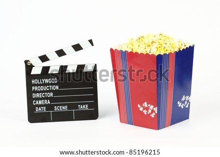 Movie clapper board and box of popcorn over white