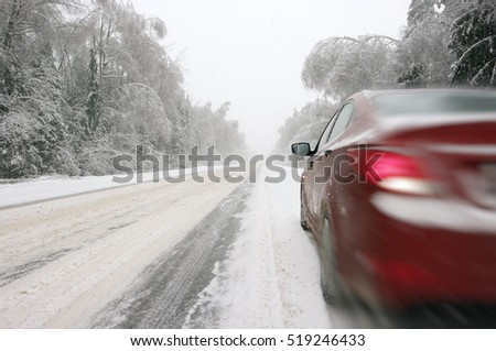 Moving car on snowy winter road among frozen forest after sleet. Cold weather, snowstorm, bad visibility, slippery road. Moscow area.