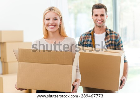 Moving to a new house together. Cheerful young couple holding cardboard boxes while other carton boxes laying on background