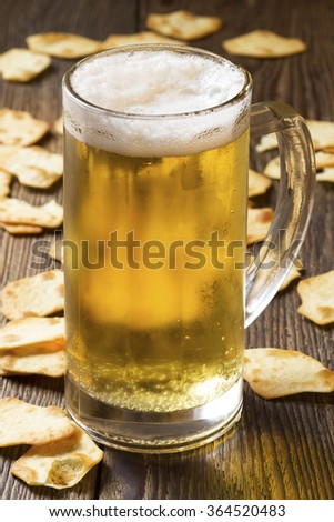 Mug of beer and crackers on wooden background