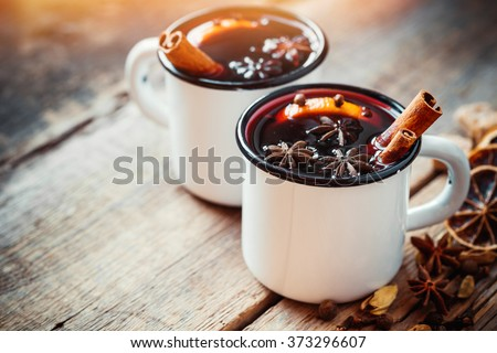 Mulled wine in white rustic mugs with spices and citrus fruit