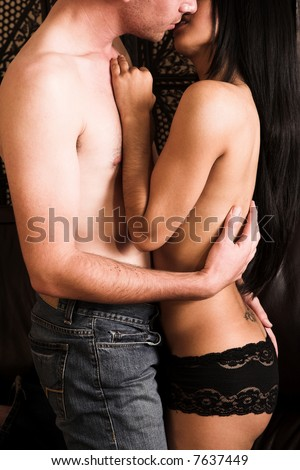 Multi-ethnic couple in passionate embrace and undressing each other in sexually active foreplay