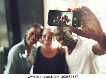 Multi ethnic friends taking a selfie with a phone