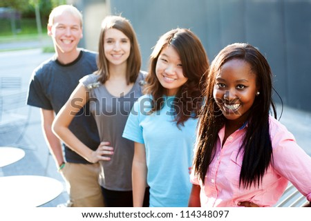 Multi-ethnic group of teenagers outside smiling