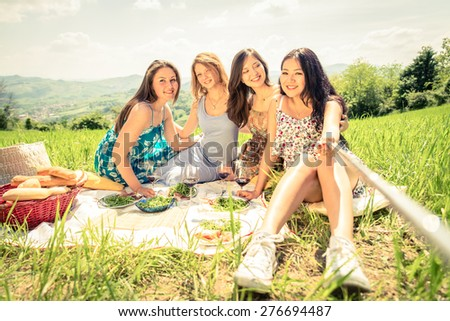 Multi-ethnic group of women enjoying picnic in the countryside and taking a picture with selfie stick - Four girls on vacation having fun