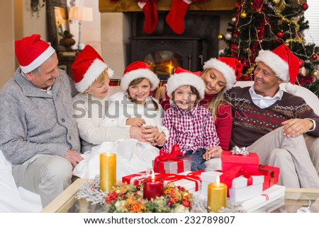 Multi generation family sitting on a couch during christmas at home in the living room