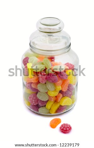Multicolor bonbons in glass pot on the white background