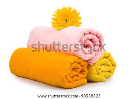 Multicolour towels rolls and flower on white background