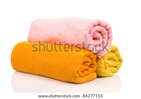 Multicolour towels rolls reflected on white background