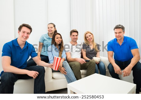 Multiethnic Friends Sitting On Couch Watching Television