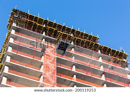 Multilevel commercial high-rise building construction with blue sky