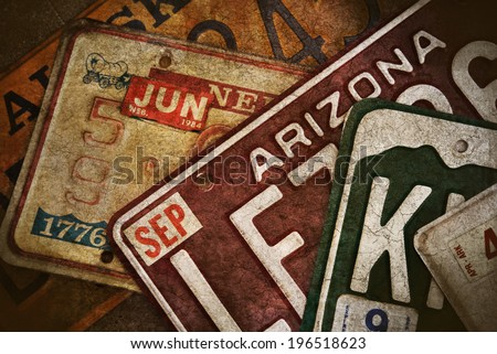 Multiple License Plates From Several United States. The color photo has a grunge texture applied to make it look old and worn.