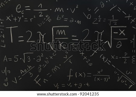 Multiple physical formulas written on a blackboard