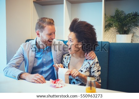 Multiracial couple dating. Handsome redhead man with beautiful Afro american woman having some good time in cafe bar or restaurant.