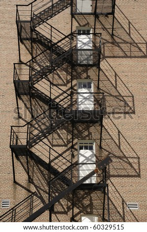 Multistory fire escape with afternoon shadows on exterior brick wall