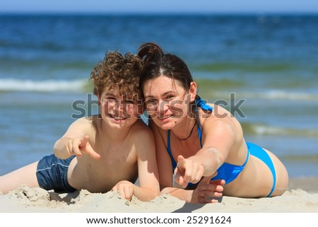 Mum and son laying on the beach