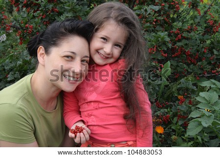 Mum with the daughter on a background of a bush of a red currant