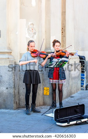 MUNICH, GERMANY - MAY 06, 2016: Two young female violinist, street musician performing in a Marienplatz square, Munich