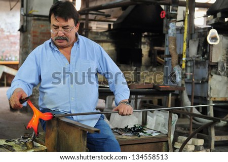 MURANO ISLAND - MAY 01 2011:Glassblowing artisan at work in a crystal glass workshop in Murano island Venice Italy.Murano glassmakers use the same tools as their ancestors have thousands of years ago
