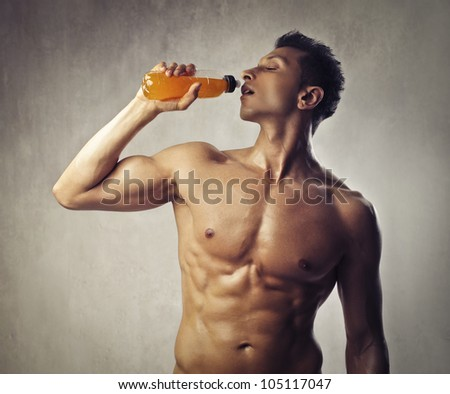 Muscular bare-chested young man having an energy drink